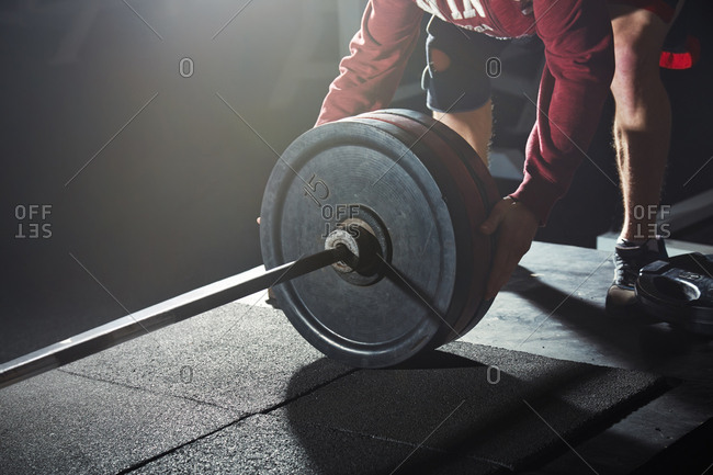 Male weightlifter exercising with barbell in gym