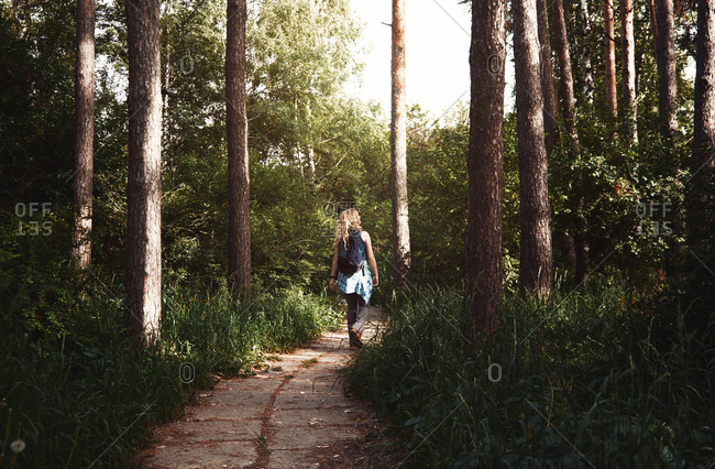 Woman with backpack walking in a public park