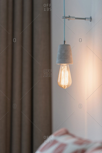 Retro lightbulb hanging on wall above pillow