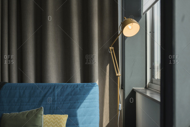 Couch with pillows and retro desk lamp near window