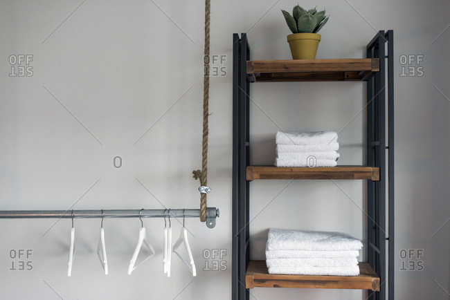 Interior of trendy hotel room with towel closet and clothes hangers on iron tube