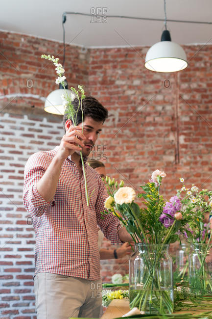 A young man arranges fresh cut flowers in a vase