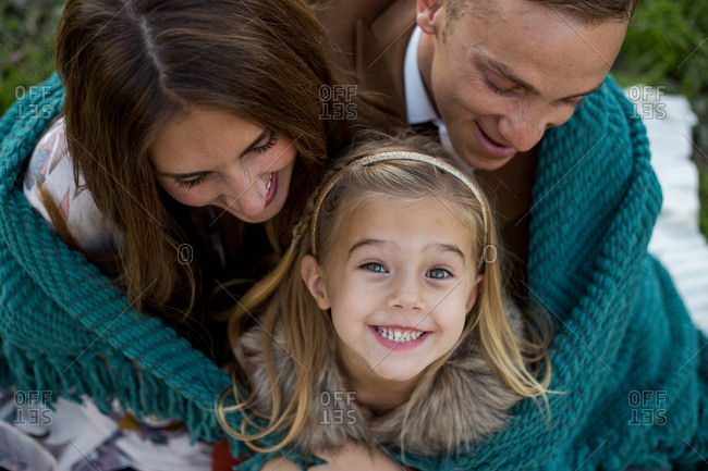 A young family of three cuddled around their daughter who is looking up at the camera
