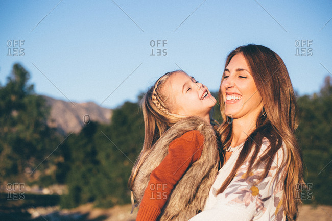 Mom holding young daughter while both are laughing