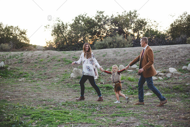 Mother, father and daughter walking outside holding hands