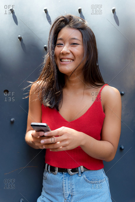 Asiatic woman texting with her smartphone on the street, Barcelona, Spain