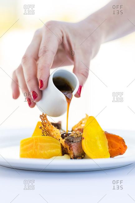 Pouring gravy on a seasonal dish