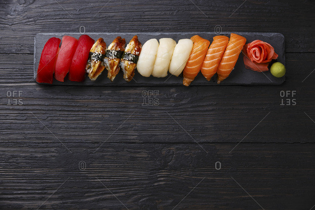 Nigiri Sushi set on stone slate on dark wooden background copy space