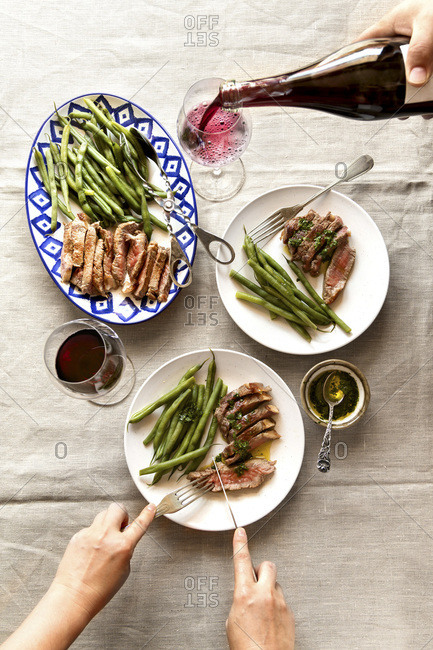 Couple serving grilled steak, cooked green beans and red wine for lunch. Top view