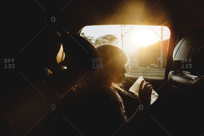 Girl drinking from cup in car