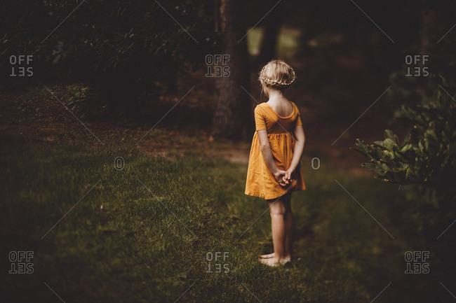 Girl standing in yard alone in dress