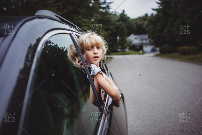 Girl looking out car window in street