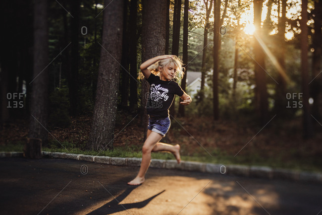 Girl running in street by woods