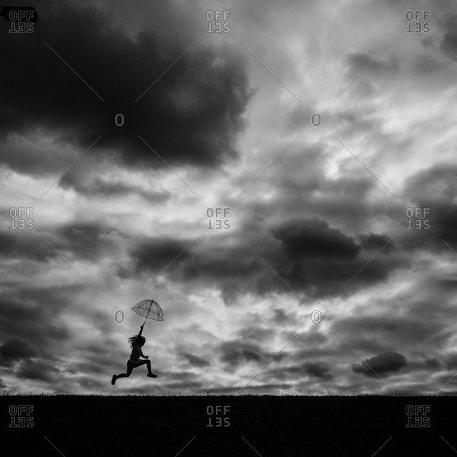 Girl with umbrella under stormy sky