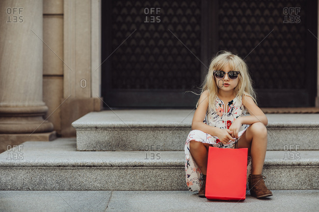 Girl in sunglasses with shopping bag