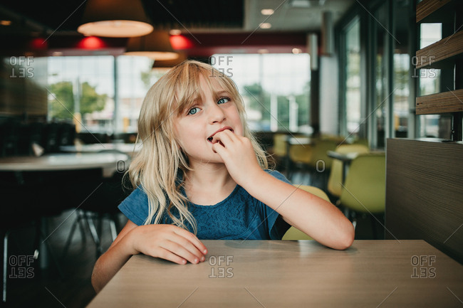 Smiling blonde girl in casual restaurant
