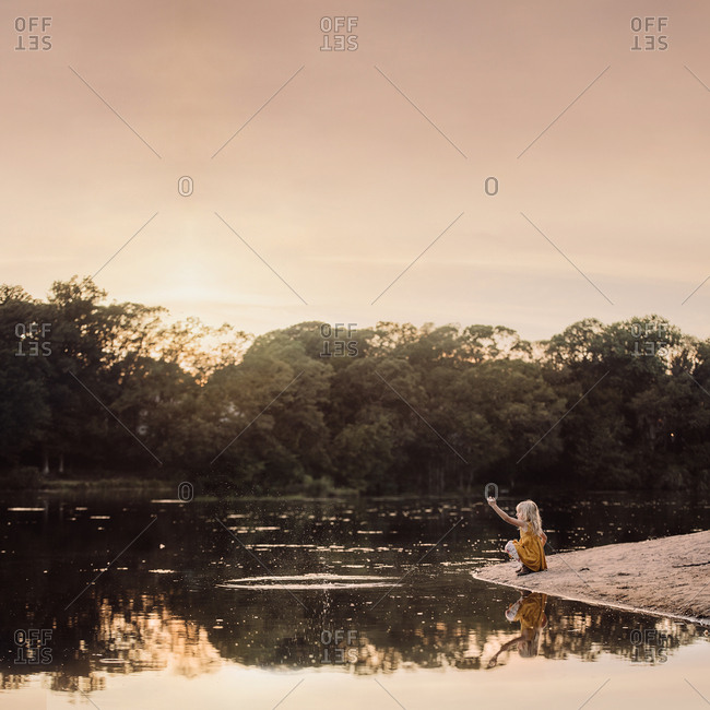 Girl throwing rocks into lake