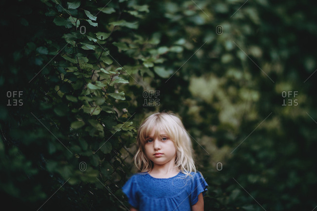 Girl looking sad by a bush