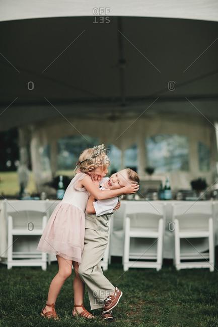 Flower girl hugging boy at wedding