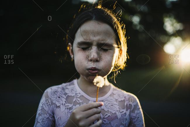 Girl making a dandelion wish
