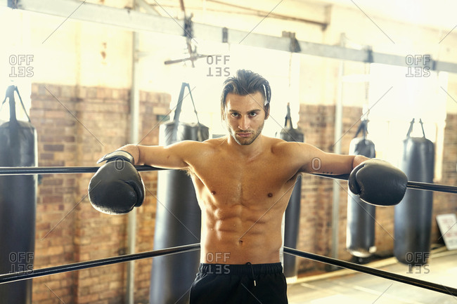 Confident Hispanic boxer leaning on ropes in boxing ring