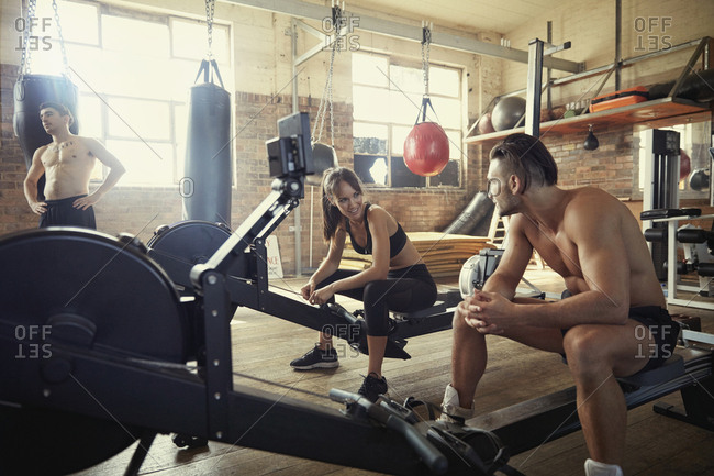 People resting on exercise equipment in boxing gymnasium