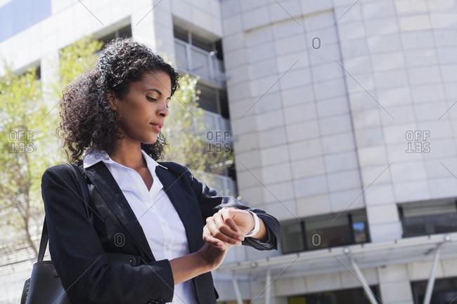 Mixed Race businesswoman checking wristwatch outdoors