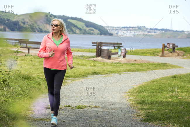 Older Caucasian woman running on path in park