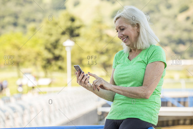 Older Caucasian woman texting on cell phone outdoors