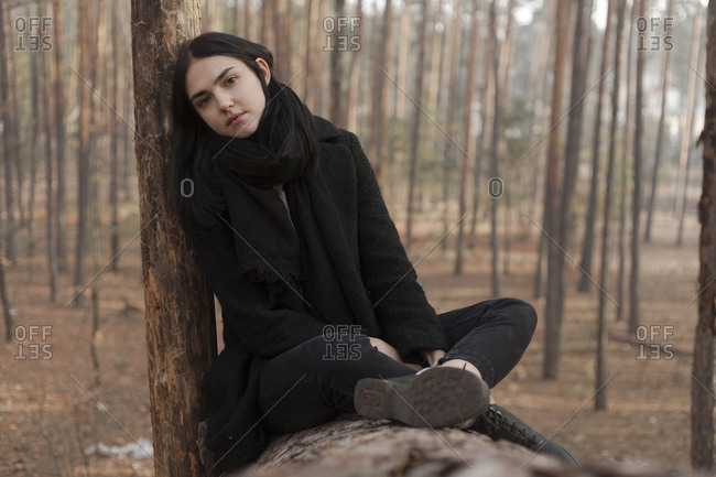 Serious Caucasian woman sitting on log in forest