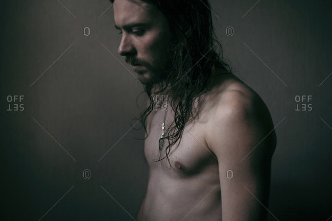 Pensive Caucasian man with long hair and bare chest
