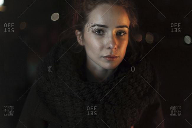 Portrait of serious Caucasian woman wearing scarf at night