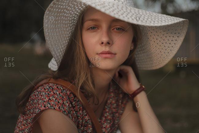 Portrait of serious Caucasian teenage girl wearing sun hat