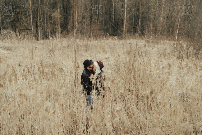 Distant Middle Eastern couple kissing in field
