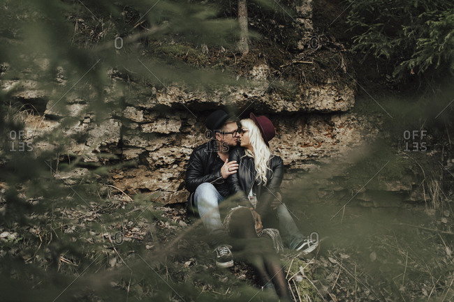 Affectionate Middle Eastern couple kissing near rocks