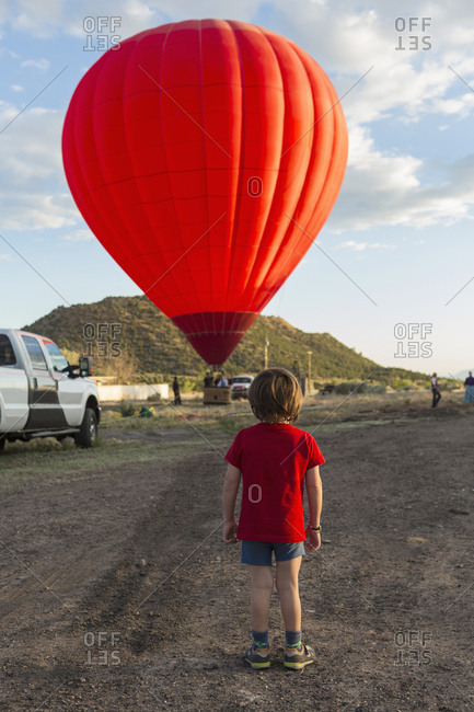 Caucasian boy watching distant hot air balloon