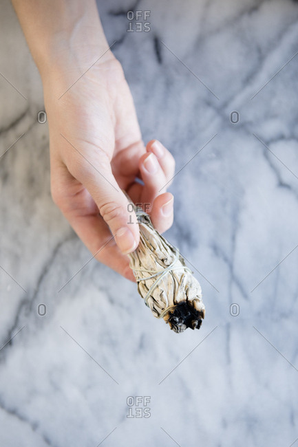 Hand of Caucasian woman holding a ritual incense