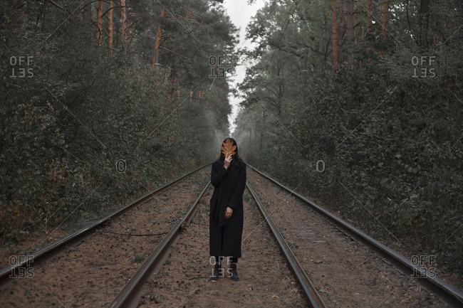 Caucasian woman holding autumn leaf on train tracks in forest