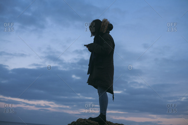 Caucasian woman wearing coat texting on cell phone at sunset