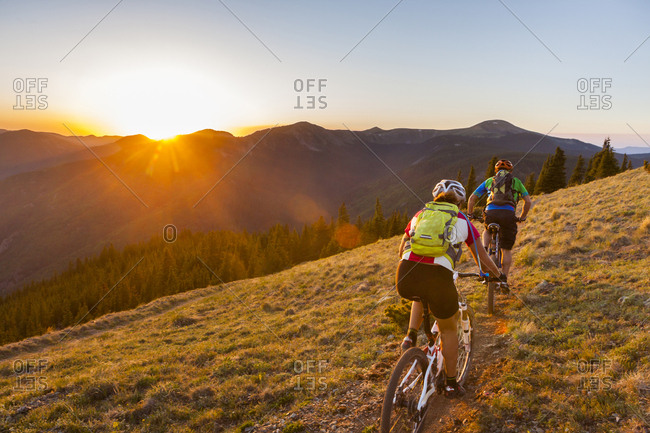 Caucasian couple mountain biking on trail