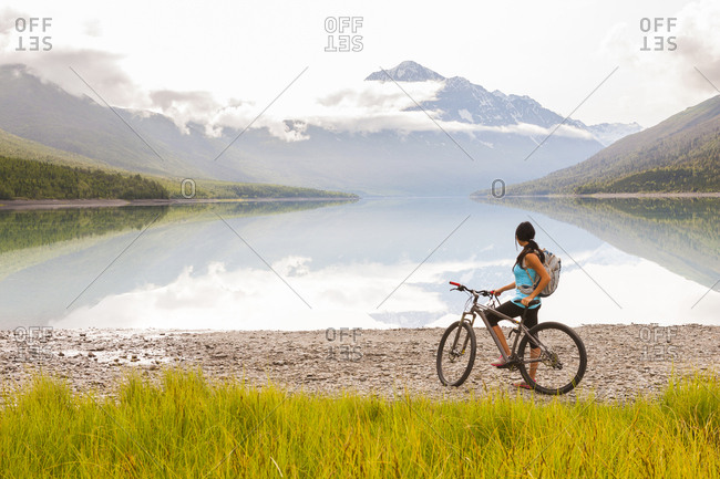 Mixed Race woman riding a bicycle near lake