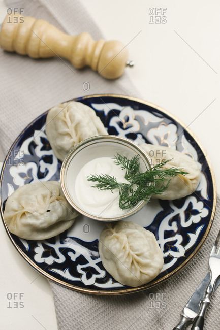Dumplings and sauce on plate with fork and knife