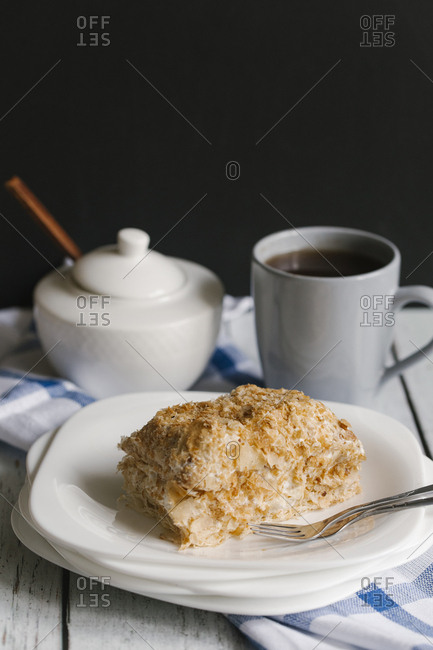 Flaky pastry on plate with coffee