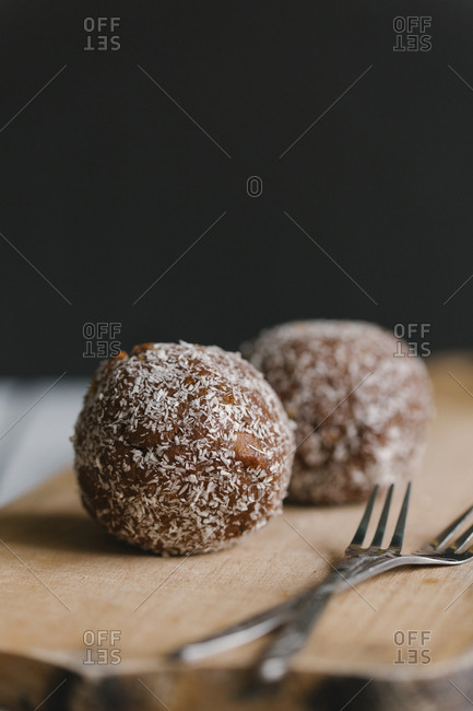 Chocolate balls with forks on cutting board