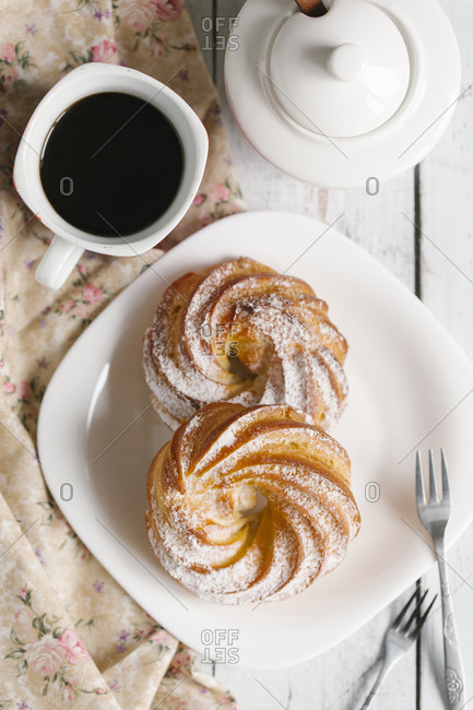 Pastry with powdered sugar on plate with coffee