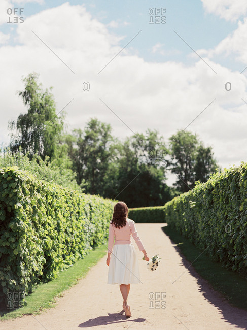 Bride walking down garden path wearing pink jacket