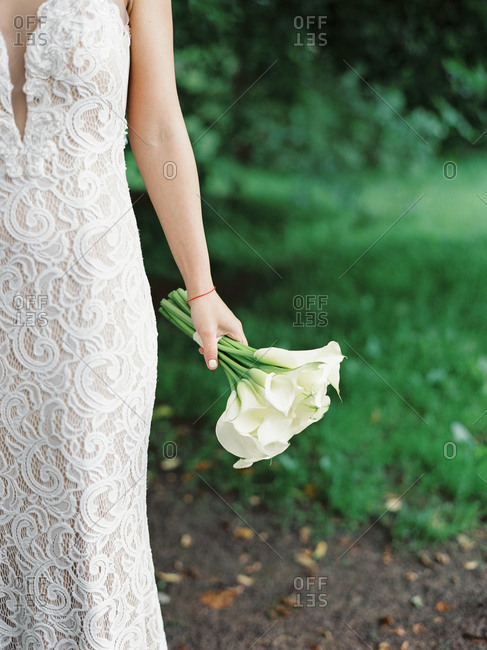 Bride holding bouquet of white calla lilies