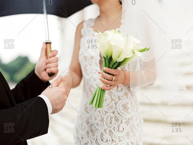 Groom taking bride's hand under an umbrella