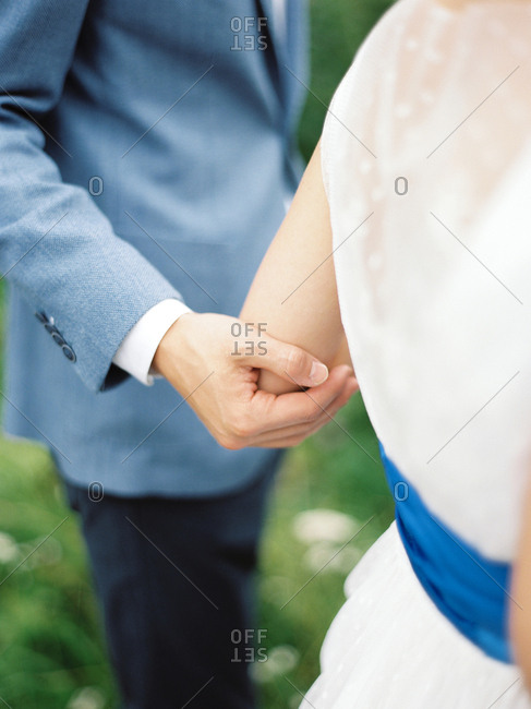 Groom holding his bride's arm