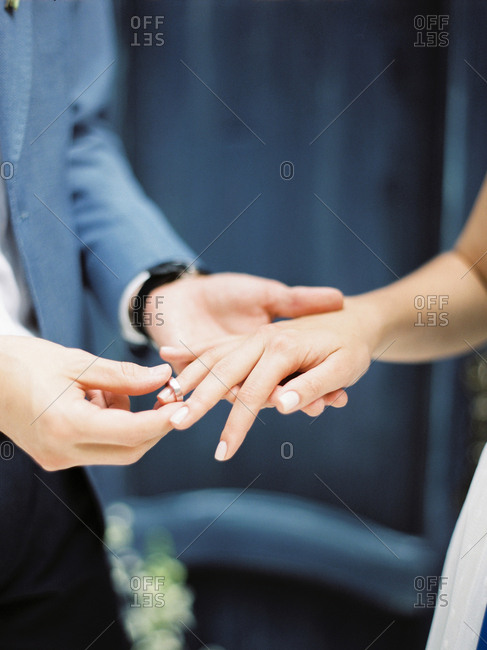 Groom placing wedding ring on his bride's hand